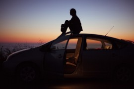 Image of a person sitting on the roof of a car and looking off in the distance silhouetted against a colorful sunset